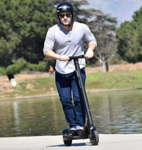 man riding the scooter by the riverwalk